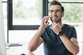 Fotografie pohledný usměvavý mladý muž v brýlích, mluví o smartphone na pracovišti