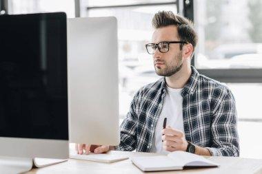 focused young man in eyeglasses working with desktop computer