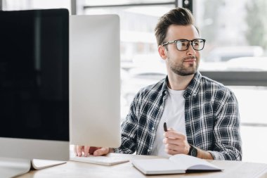 handsome young man in eyeglasses looking away while using desktop computer at workplace