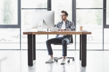 full length view of handsome young programmer using desktop computer at workplace