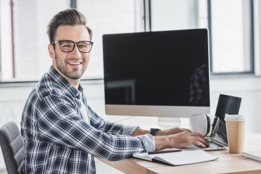 handsome young programmer in eyeglasses smiling at camera while working with laptop and desktop computer