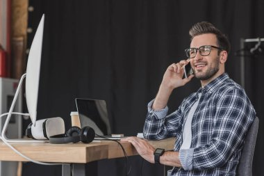 smiling young man in eyeglasses talking by smartphone and looking away at workplace