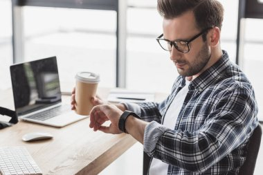 young man in eyeglasses holding coffee to go and checking smartwatch at workplace
