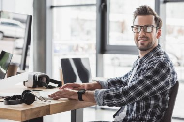 handsome young man in eyeglasses smiling at camera while working with desktop computer and laptop