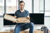 pohledný mladý programátor v brýle drží pizzu a usmívá se na kameru