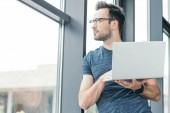Fényképek csinos, fiatal férfi a szemüvegek gazdaság laptop és látszó-on ablak