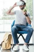 usměvavý mladý muž drží jablko a použití soupravu pro virtuální realitu