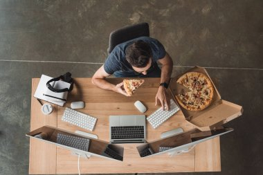 overhead view of programmer eating pizza and using computers at workplace
