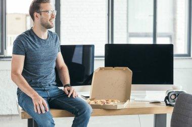 Genç adam uzak masaüstü bilgisayarlar ve pizza ile masada otururken seyir gözlük gülümseyen