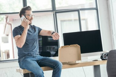 Masaüstü bilgisayarlar ve pizza ile masada otururken smartphone ile konuşurken gözlük yakışıklı genç programcı