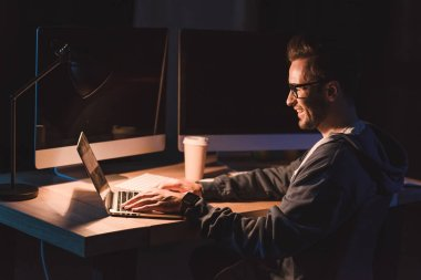 smiling young programmer in eyeglasses using laptop while working at night