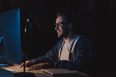 smiling young programmer in eyeglasses working with desktop computer at night