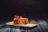 mrkvový dort s náplní berry a plátek pomeranče na štítku na dřevěný stůl