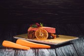 Fotografie close up view of carrot cake with berry filling, mint, orange slice on plate near carrots on wooden table