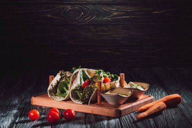 selective focus of tortillas with falafel, cherry tomatoes and germinated seeds of sunflower on wooden tray with sauces near carrots