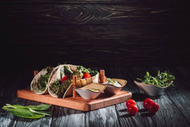 food composition of tortillas with falafel, cherry tomatoes and germinated seeds of sunflower on wooden tray with sauces on table