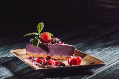 selective focus of blueberry cake with strawberries, mint and viola petals on plate on wooden table