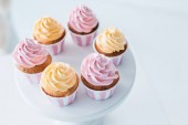 selective focus of delicious cupcakes on stand at table