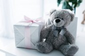 selective focus of teddy bear with gift boxes on table