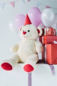 teddy bear in cone with gift boxes and air balloons