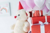 Fotografie selective focus of teddy bear in cone with gift boxes and air balloons