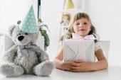 Fotografie happy birthday kid sitting with present at table with teddy bear in cone