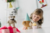 cute birthday kid feeding teddy bear in cone by cupcake at table