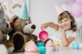 Fotografie smiling birthday child having tea party with teddy bears in cones