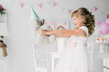 side view of smiling birthday child holding teddy bear in cone