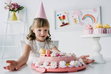 Surprised little child with wide arms looking at birthday cake stock vector