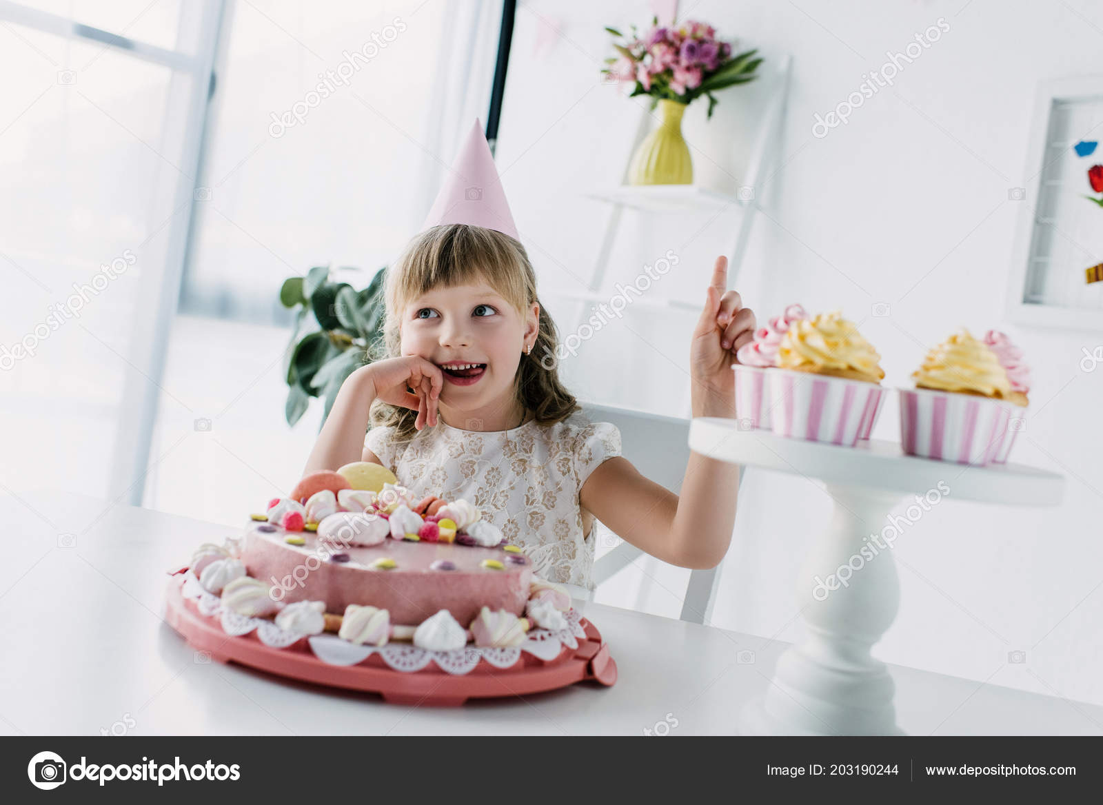 Smiling Birthday Kid Cone Doing Idea Gesture While Sitting Table Stockfoto