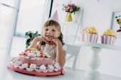 šťastné dítě v kuželu sedí u stolu s narozeninový dort a koláčky