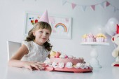 Fotografie happy adorable child in cone sitting at table with birthday cake