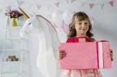 Photo smiling birthday kid holding gift box near decorative unicorn