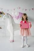 Photo cute birthday child holding gift box near decorative unicorn