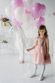 Photo smiling birthday child holding bunch of air balloons and standing with decorative unicorn