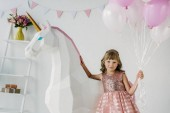 Photo adorable little kid holding bunch of air balloons and standing with decorative unicorn