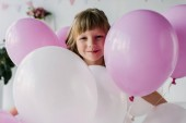 Fotografie portrait of smiling adorable child standing with air balloons