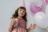low angle view of birthday kid with dirty nose eating cupcake near bunch of pink balloons