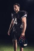 Fotografie sportovní americký fotbalista v černé uniformě drží helmu a koukal na černém pozadí