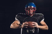 Fotografie mad american football player holding ball in hands and looking at camera isolated on black
