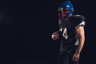 american football player in black uniform with ball in hand isolated on black