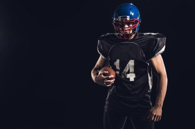young american football player with ball looking at camera isolated on black
