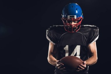 american football player looking at ball in hands isolated on black
