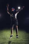 athletic american football player jumping with ball under spotlights on black
