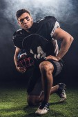 Photo attractive young american football player with helmet standing on knee on black