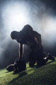 sad failed american football player standing on knees on green grass and looking down against white smoke