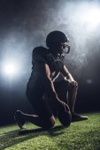 thoughtful american football player with ball standing on knee against white smoke