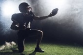 Fotografie american football player standing on knee on green grass and holding ball against white smoke