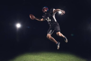 american football player jumping with ball under spotlights on black